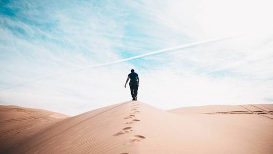 man walking on desert. Foto: nathan mc bride, unsplash